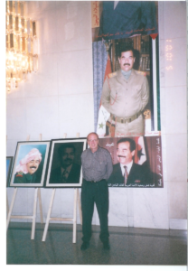 Larry poses in front of a selection of Saddam Hussein portraits.